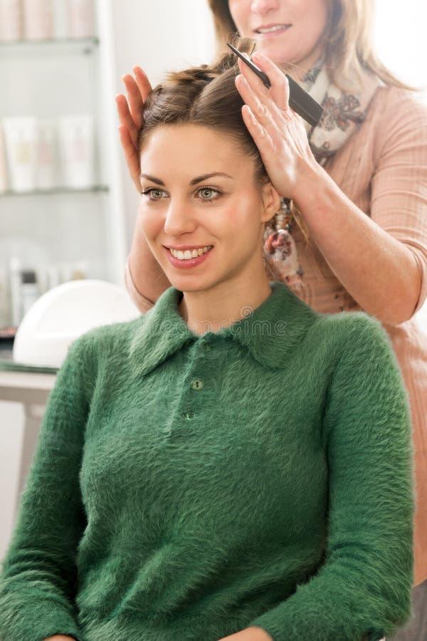 Nette lächelnde Frau im Herrenfriseursalon lizenzfreie stockbilder
