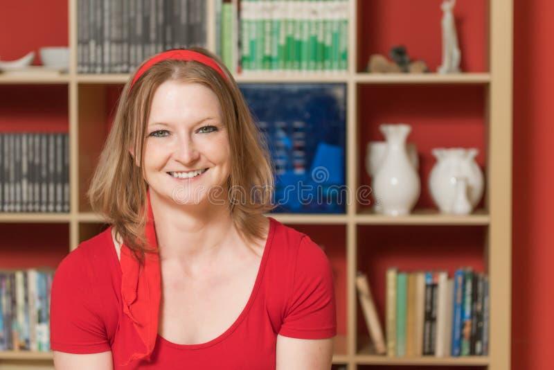 Nette lächelnde junge Frau, die in ihrem Haus aufwirft stockbilder