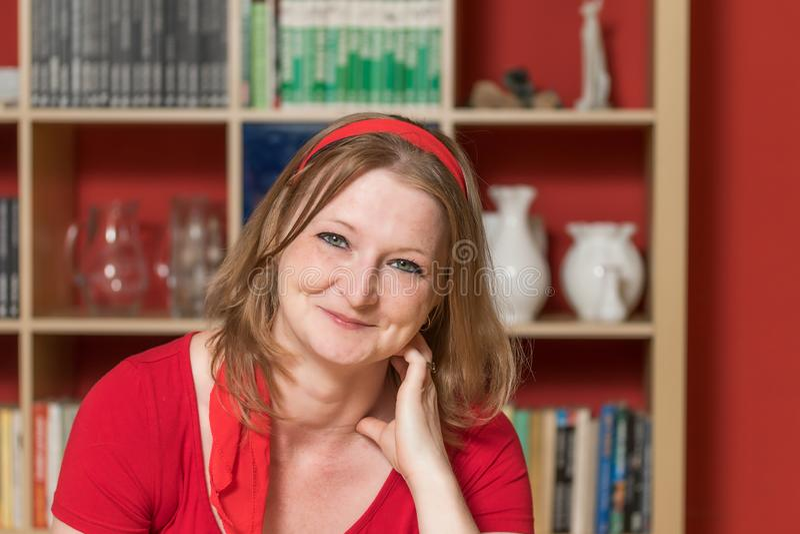 Nette lächelnde junge Frau, die zuhause aufwirft lizenzfreie stockfotos