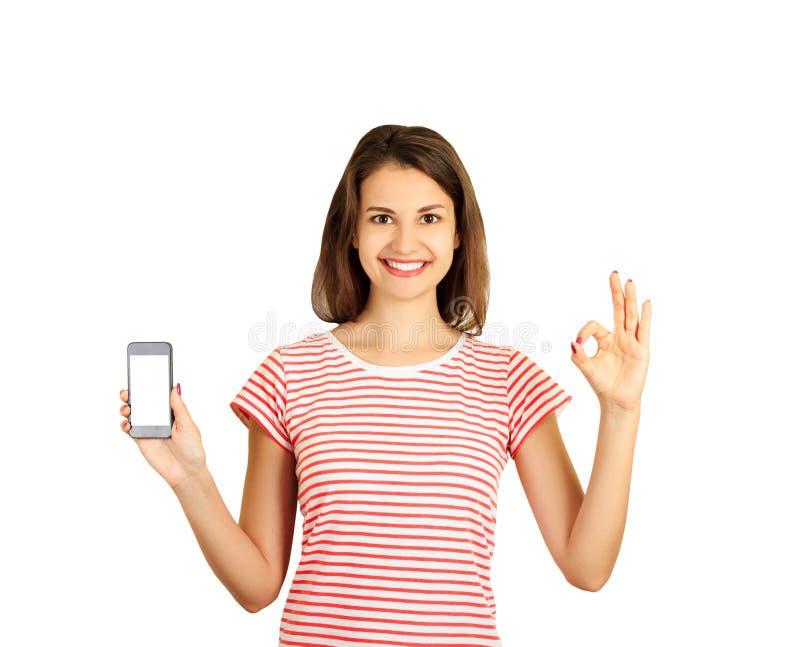 Nette lächelnde junge Schönheit hält einen modernen Smartphone und zeigt leeren Bildschirm und zeigt ein gutes Zeichen O.K. emoti stockfotografie
