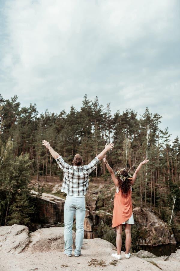 Nette liebevolle junge Paare, die frei und bei der Stellung am Rand des Felsens glücklich sich fühlen stockbild