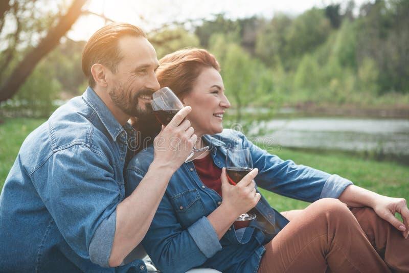 Nette liebevolle Paare, die Flussansicht genießen stockfotos