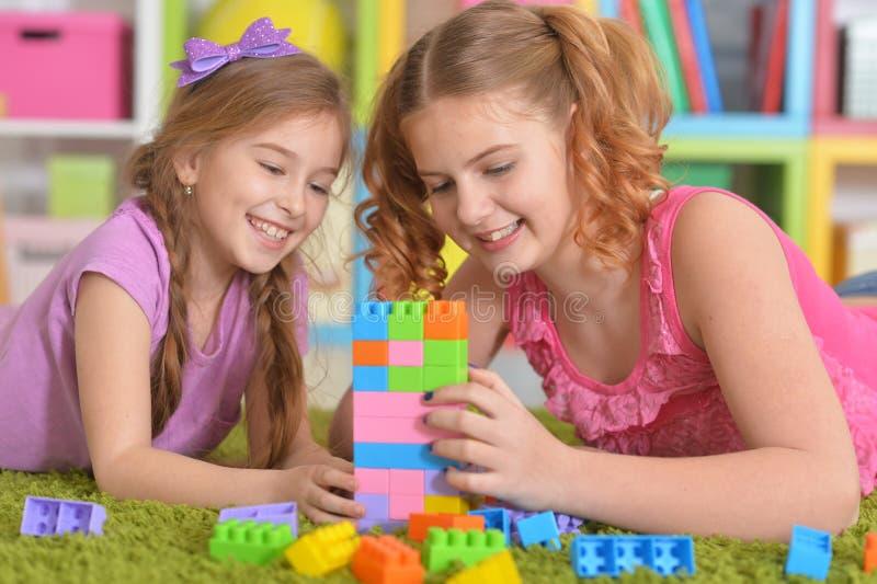 Nette Mädchen, die mit bunten Plastikblöcken spielen stockfotografie