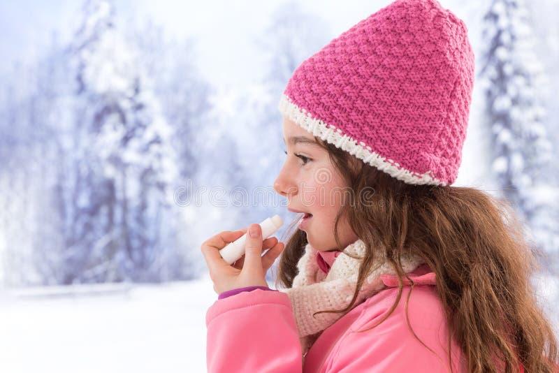 Nette Mädchenkleidung, die Lippenbalsam anwendet stockfoto