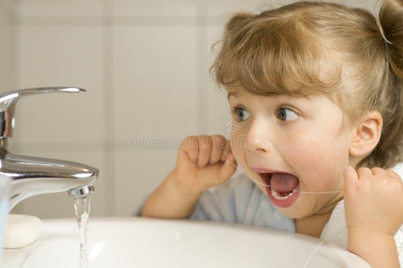 Nette Mädchenreinigungszähne durch Glasschlacke stockfoto