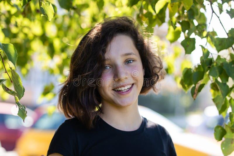 Nette M?dchenstellung des jungen jugendlich unter einem Lindenbaum umgeben durch Bl?tter stockfotos