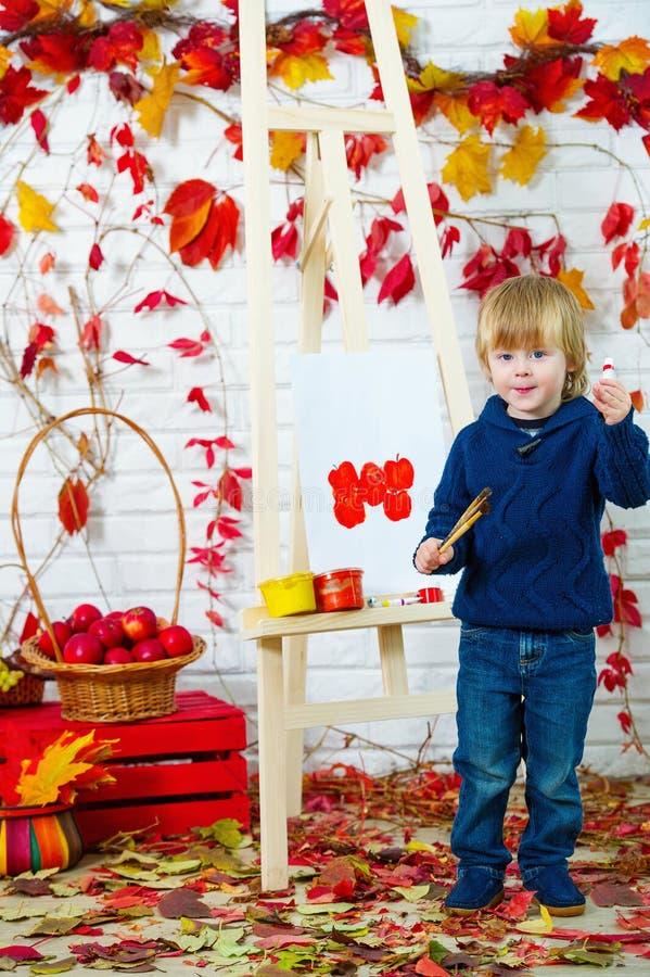 Nette Malereiäpfel des kleinen Jungen im Herbst stockbilder