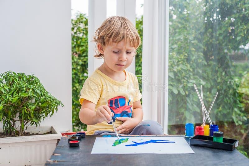 Nette Malerei des kleinen Jungen mit bunten Farben lizenzfreie stockfotografie