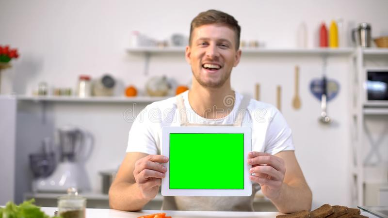 Nette Mannholdingtablette mit grünem Schirm, Blogs und Appsschablone kochend lizenzfreie stockfotos