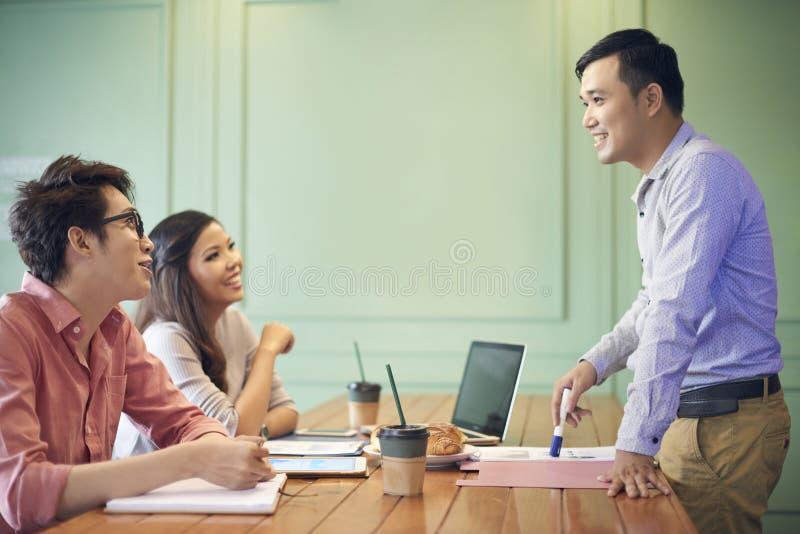 Nette Mitarbeiter, die Kaffee beim Arbeiten trinken lizenzfreie stockfotos