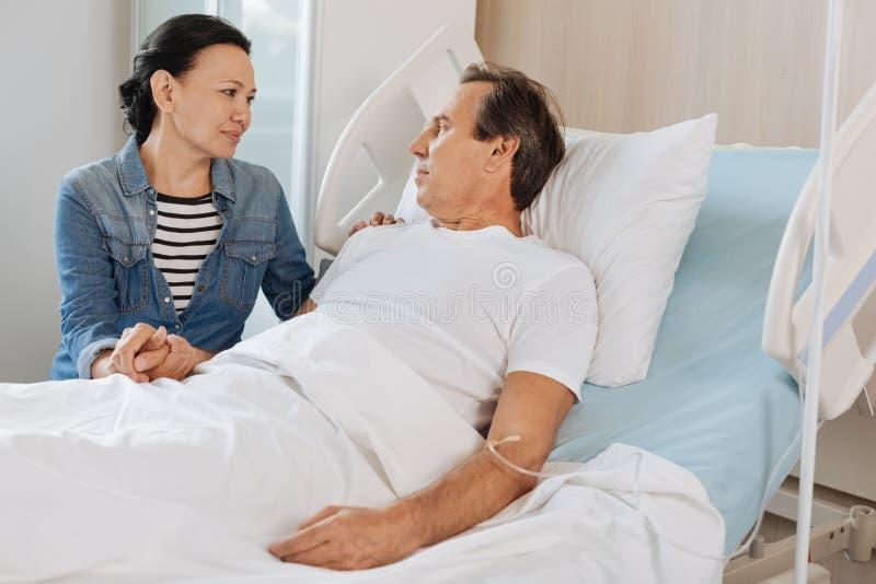Nette mitfühlende Frau, die ihren Ehemann besucht lizenzfreies stockfoto