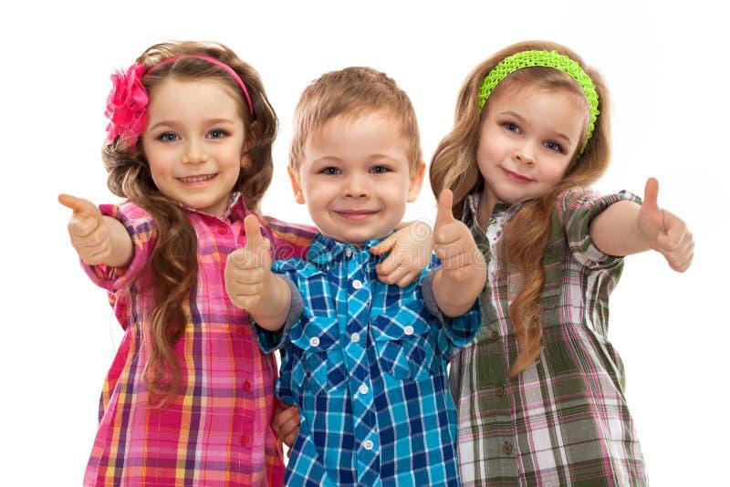 Nette Modekinder, die sich Daumen zeigen lizenzfreies stockfoto