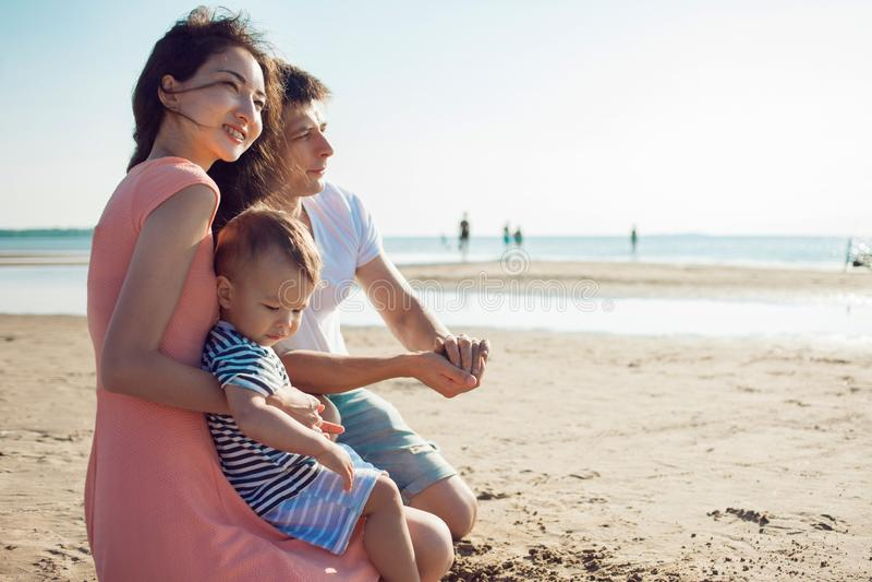 Nette multi ethnische Familie haben einen Rest auf einem Seeufer stockbild