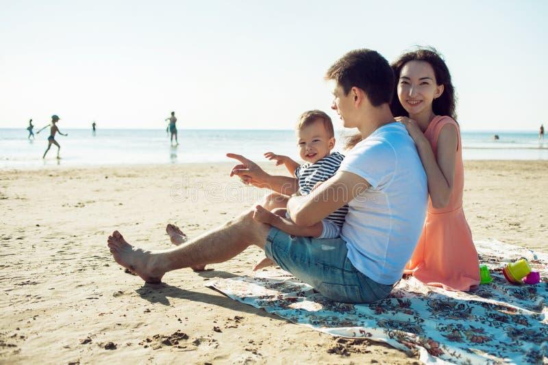 Nette multi ethnische Familie haben einen Rest auf einem Seeufer stockfoto