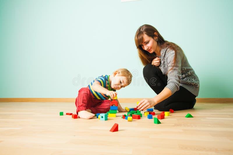 Nette Mutter, die mit ihrem Kind im Schlafzimmer spielt lizenzfreie stockfotos