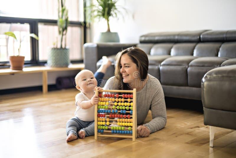 Nette Mutter, die mit seinem Baby auf Boden am Wohnzimmer spielt lizenzfreie stockfotos