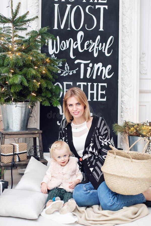 Nette Mutter umfasst ihre nette Babytochter Elternteil und kleines Kind, die Spaß nahe Weihnachtsbaum zuhause haben lieben lizenzfreies stockbild