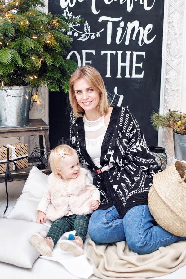 Nette Mutter umfasst ihre nette Babytochter Elternteil und kleines Kind, die Spaß nahe Weihnachtsbaum zuhause haben lieben stockbilder