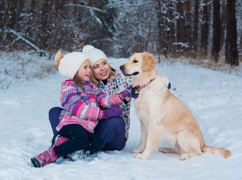 Nette Mutter und ihre nette Tochter mit ihrem Hundegolden retriever im Winter stockfoto