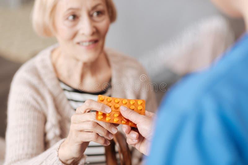 Nette optimistische Frau, die einige Vitamine empfängt lizenzfreie stockbilder