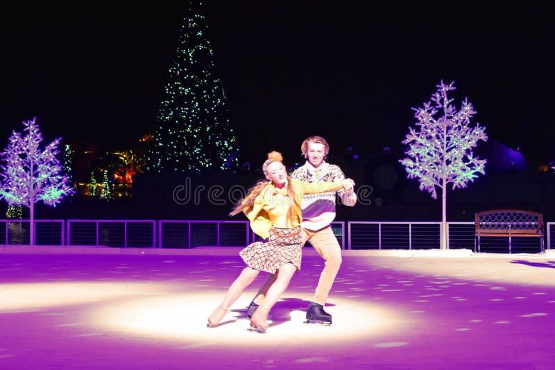 Nette Paare, die auf Eis am Weihnachtszeigung im internationalen Antriebsbereich eislaufen lizenzfreie stockbilder