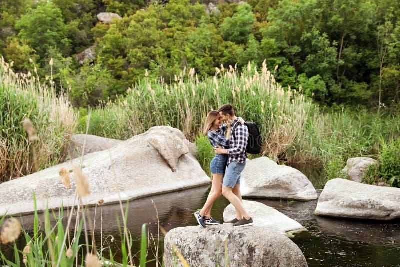 Nette Paare, die auf Stein in der Mitte von Fluss umarmen Kampierende Jahreszeit stockbild