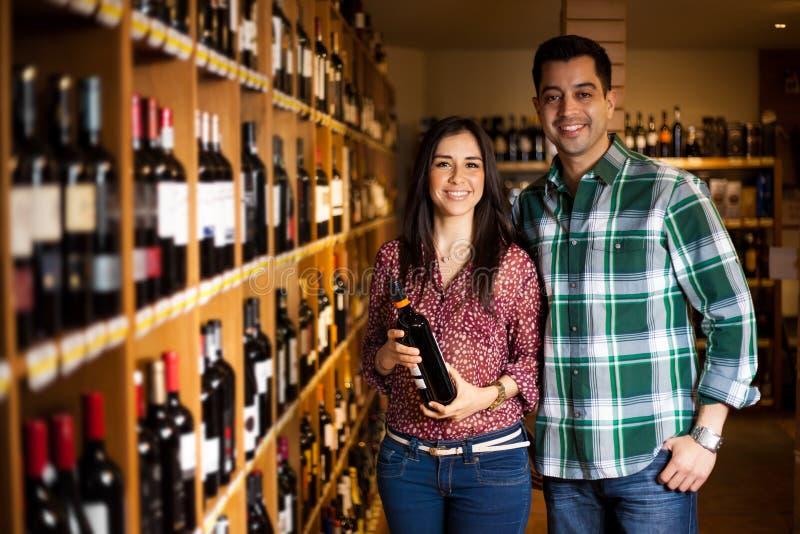 Nette Paare, die eine Flasche Wein kaufen lizenzfreie stockbilder
