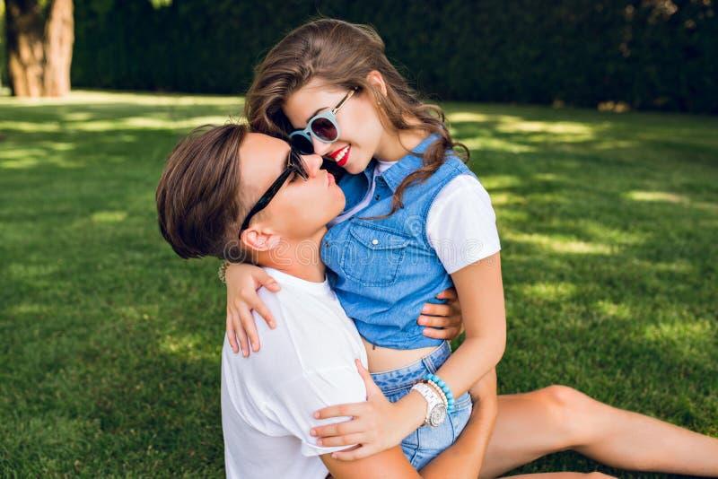 Nette Paare von jungen Leuten auf Gras im Park Hübsches Mädchen mit dem langen gelockten Haar in der Jeanskleidung sitzt auf hübs lizenzfreie stockfotos