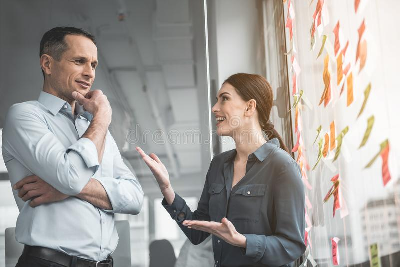 Nette Partner, die im Büro sprechen stockfotografie