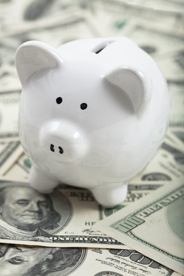 Nette Piggy Querneigung auf Haufen des Bargeldes stockbilder