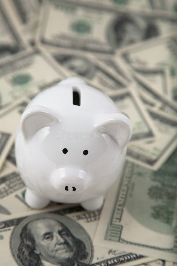 Nette Piggy Querneigung auf Haufen des Bargeldes stockbild
