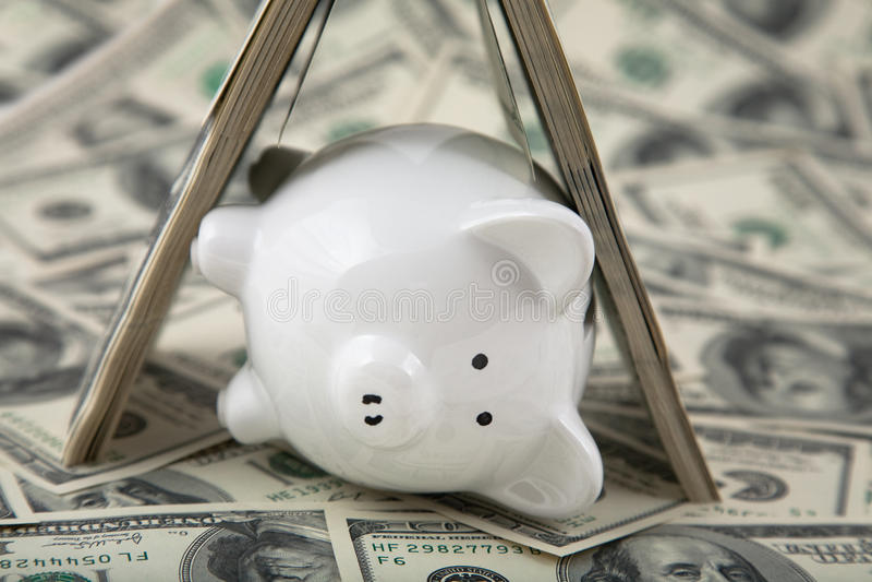 Nette Piggy Querneigung unter Schutz des Bargeldes stockfotografie
