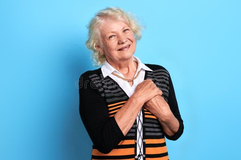 Nette positive alte Frau mit den Händen auf dem Kastenlächeln, die Kamera betrachtend stockfotografie