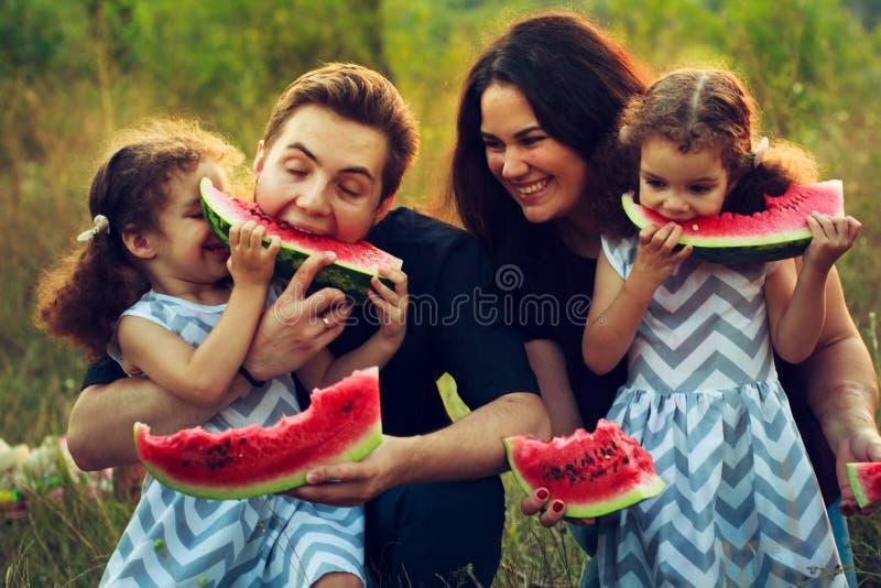 Nette positive vierköpfige Familie, die ein Picknick hat und draußen Wassermelone in einem sonnigen Wetter isst Gelockte schöne Z lizenzfreie stockfotos
