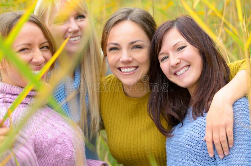 Nette recht junge Frau, die an der Kamera grinst stockfotos
