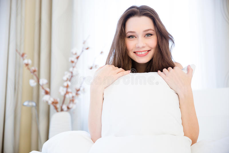 Nette recht junge Frau, die im Bett sitzt und Kissen hält lizenzfreie stockfotografie