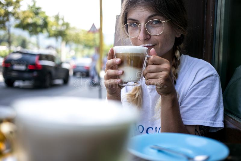 Nette recht junge Frau trinkt Kaffeemilchschaum stockbild