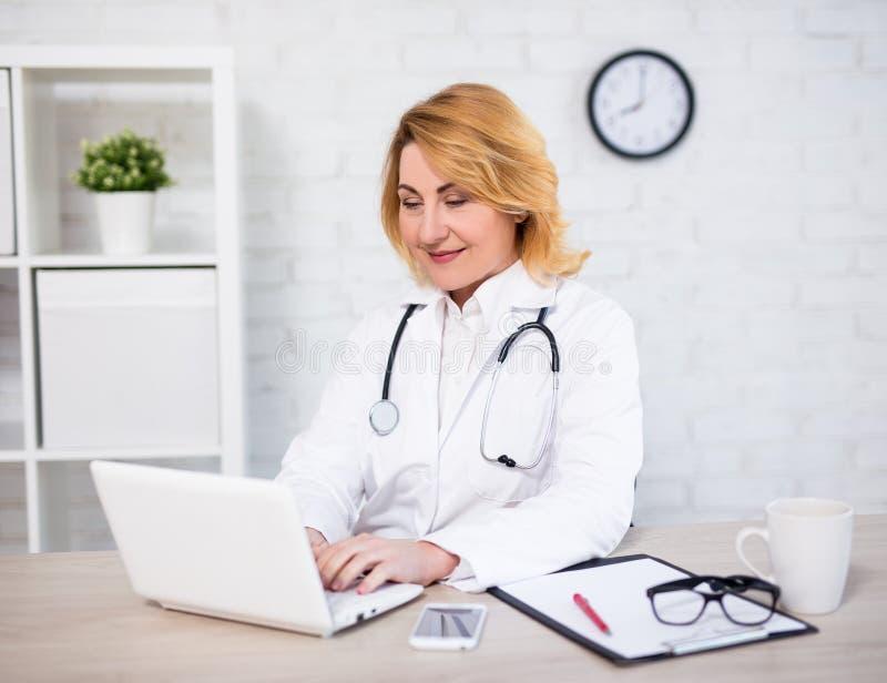 Nette reife Ärztin oder Krankenschwester, die mit Laptop im Büro arbeiten lizenzfreie stockfotografie