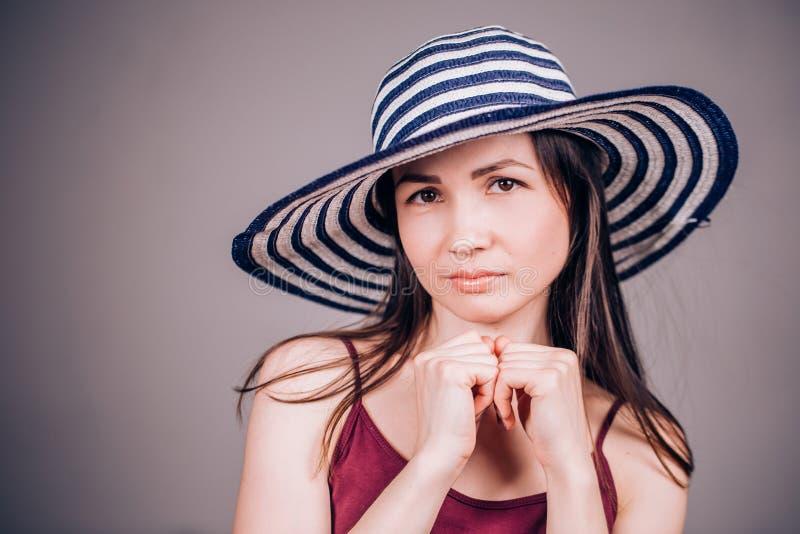 Nette reizend Brunettefrau in gestreiften Hutblicken glücklich und mit einem Lächeln in camera auf grauem Hintergrund Sommer, Glü lizenzfreie stockbilder