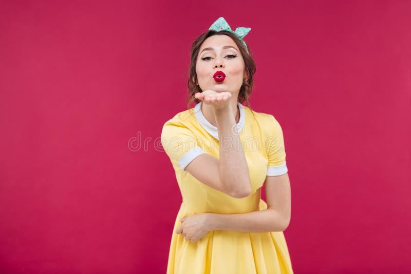 Nette reizend junge Frau, die einen Kuss steht und sendet lizenzfreies stockfoto
