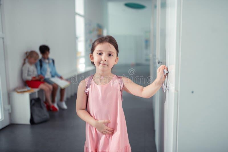 Nette reizende dunkeläugige Schulmädchenstellung nahe ihrem Schließfach lizenzfreie stockfotografie
