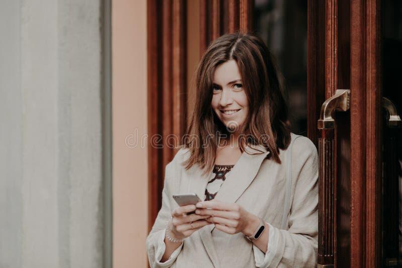 Nette reizende Frau des Brunette simst E-Mail-Buchstaben, benutzt Handy und der freie Internetanschluss, gekleidet in der weißen  lizenzfreies stockfoto