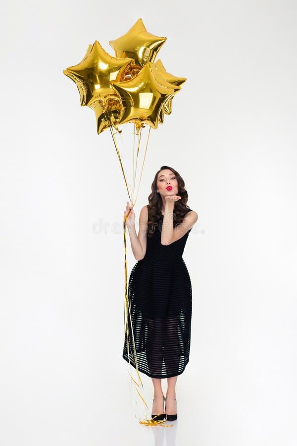 Nette reizende Frau mit den sternförmigen Ballonen, die einen Kuss senden lizenzfreie stockfotografie