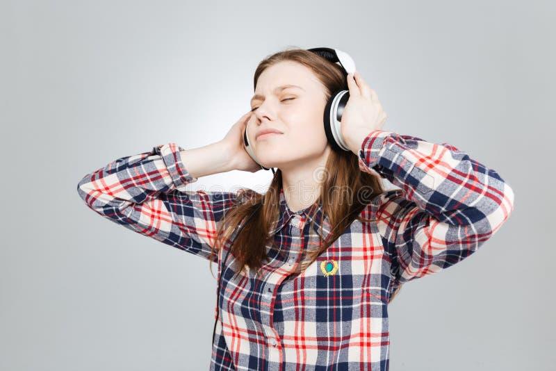 Nette reizende Jugendliche, die Musik in den Kopfhörern hört lizenzfreie stockbilder