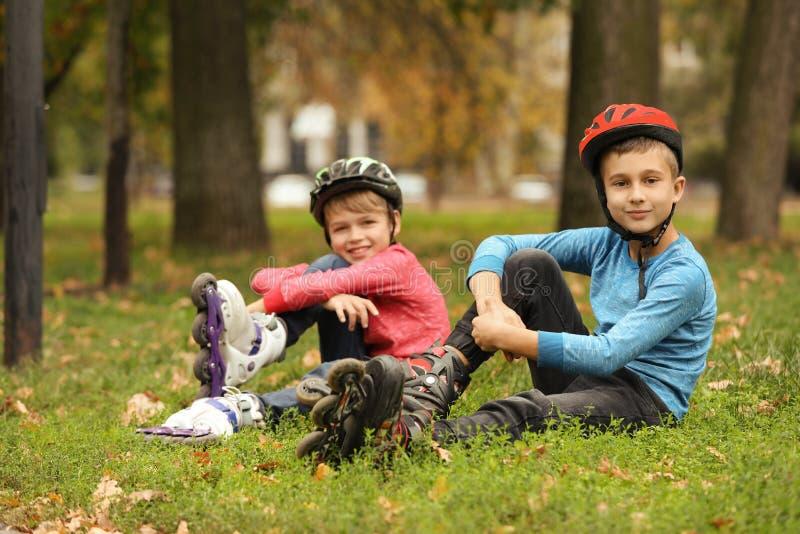Nette Rollenschlittschuhläufer, die auf Gras sitzen stockfotografie