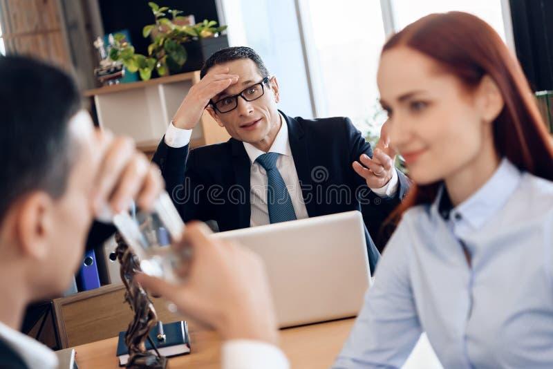 Nette rothaarige Frau betrachtet Mann, Trinkglas Wasser in Rechtsanwalt ` s Büro für Scheidung stockbild