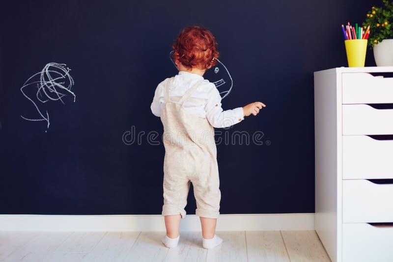 Nette Rothaarigebabyzeichnung auf der Kreide ummauern zu Hause lizenzfreie stockfotos
