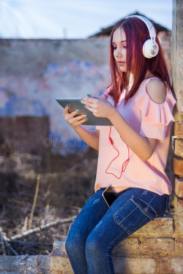 Nette Rothaarigedame mit digitaler Tablette hörend Musik in den Kopfhörern auf Ruinenwandroten backsteinen des Retro- Hauses im S lizenzfreie stockfotos