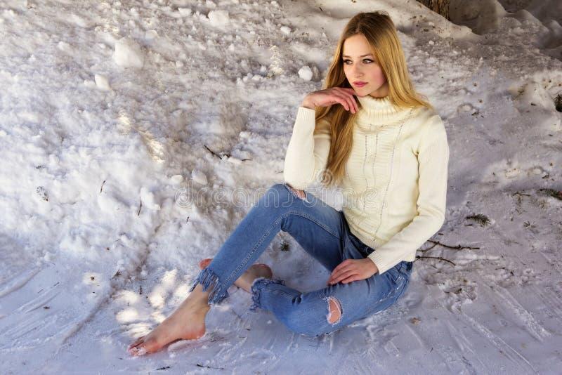 Nette schöne Jugendliche, die im Schnee sitzt stockfoto