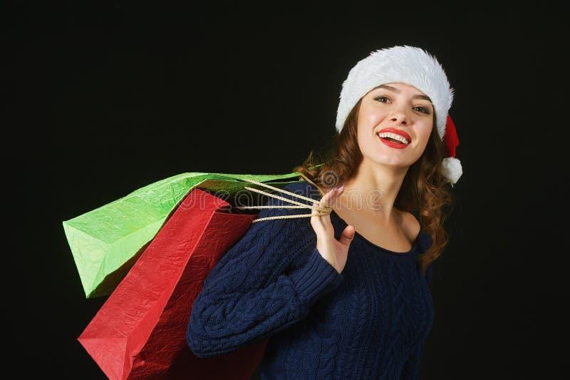 Nette schöne junge Frau im Hut von Santa Claus mit Paketen auf einem dunklen Hintergrund stockfotografie